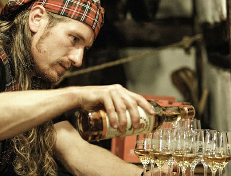 Whiskykenner schenkt viele Whiskys für ein Tasting ein