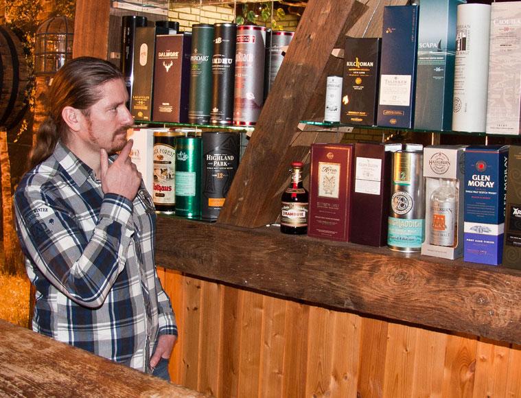 Mann blickt auf Whiskyregal