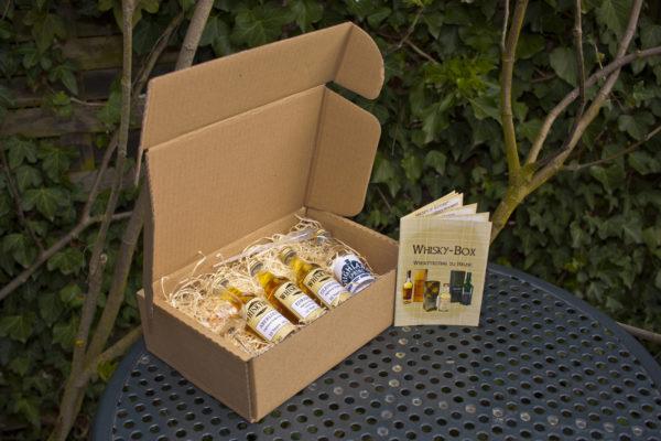 Die Whiskybox - Whisky Tasting zu Hause - steht auf einem Tisch im Garten.