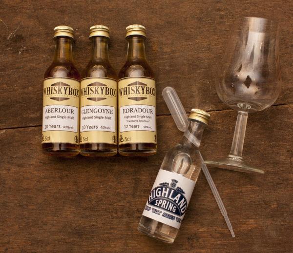 Flaschen, Pipette und Glas der Whiskybox - Whisky Tasting zu Hause - liegen auf einem Holzuntergrund.