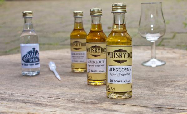 Flaschen, Pipette und Glas der Whiskybox - Whisky Tasting zu Hause - stehen auf einem Fassdeckel.