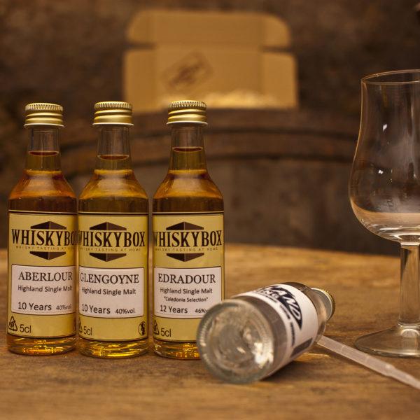 Flaschen und Utensilien der Whiskybox - Whiskytasting zu Hause - stehen vor einem Fass, auf dem ein Karton steht.