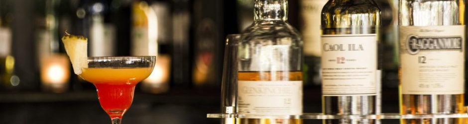 Whisky Cocktail mit Ananas neben Whisky-Flaschen