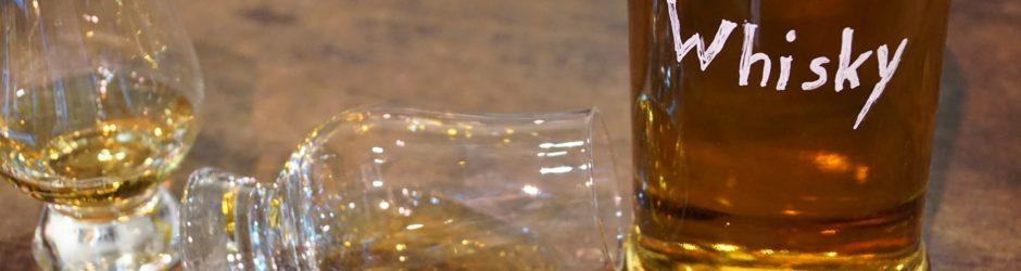 Eine Flasche mit der Aufschrift Whisky, zwei Whiskygläser und Schokolade