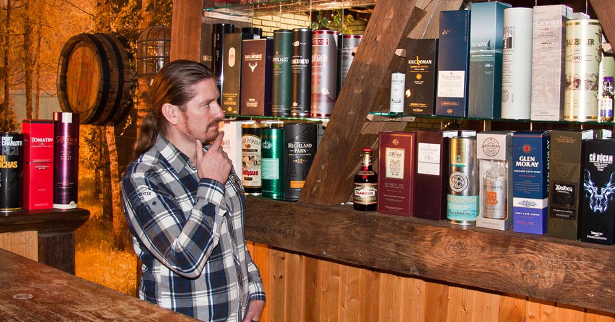 Mann steht vor einem Whiskyregal